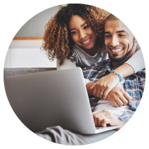 A happy young couple looks at the computer.